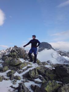 Bjørn Bye poserer på toppen av Vestre Austanbotntind. Ringstind i bakgrunnen